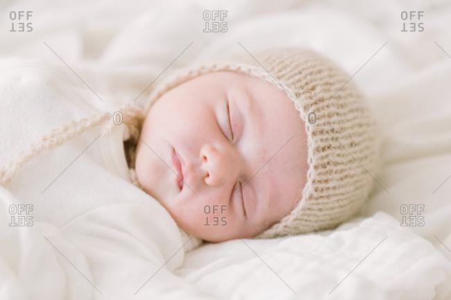 Newborn baby in knit bonnet sleeping on white bed