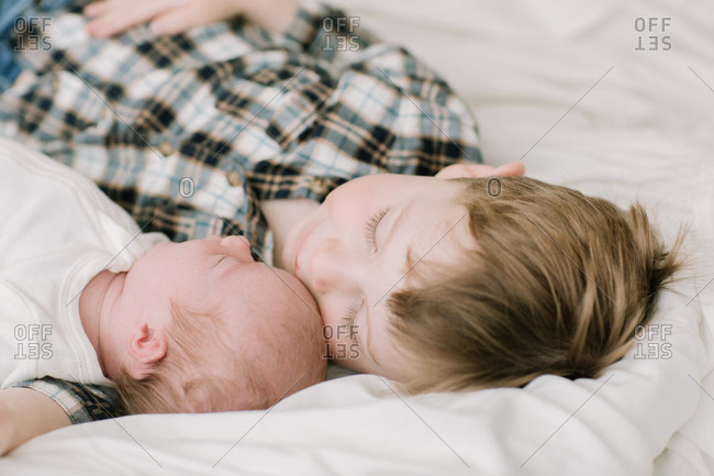 Big brother and newborn baby sister snuggling on bed