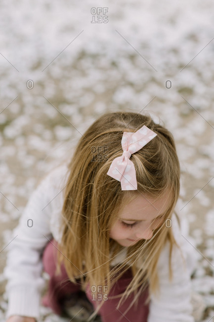 Preschool girl looking down at ground outside