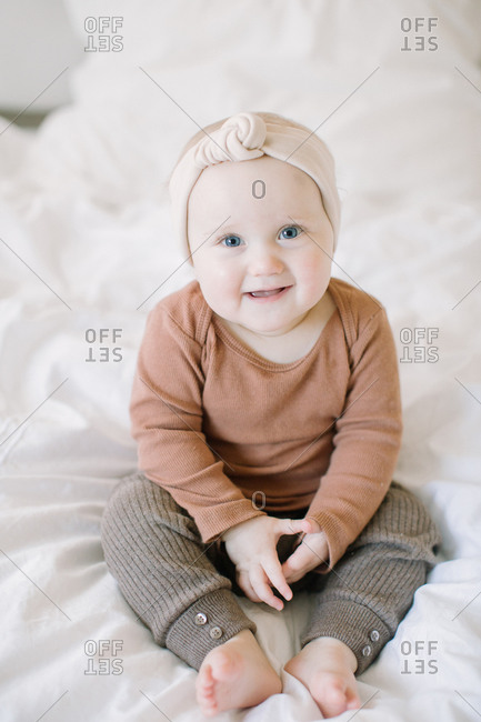 Baby girl sitting up on bed and smiling at camera