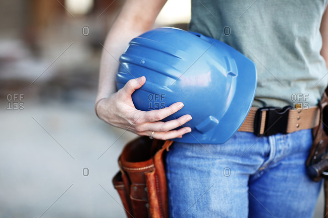 Close up of a female construction worker holding a hard hat