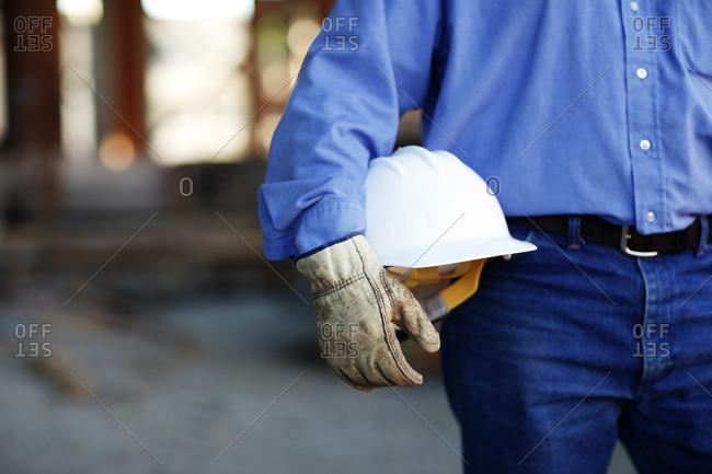 Close up of a male construction foreman worker holding a hard ha