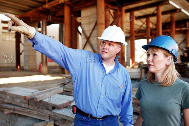 Male construction foreman giving directions to construction work
