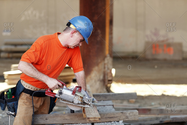 Male construction worker making wood cut