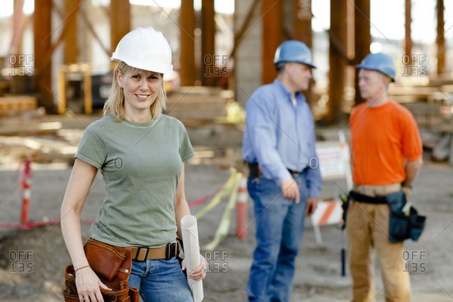 Portrait of female construction worker with two workers behind