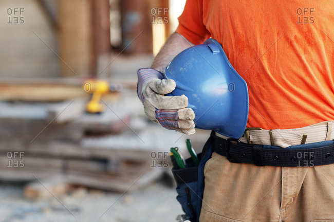 Close up of a male construction worker holding a hard hat