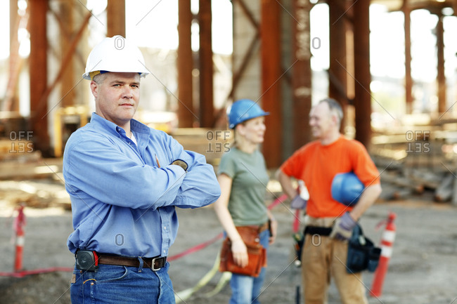 Portrait of male construction foreman with two workers behind