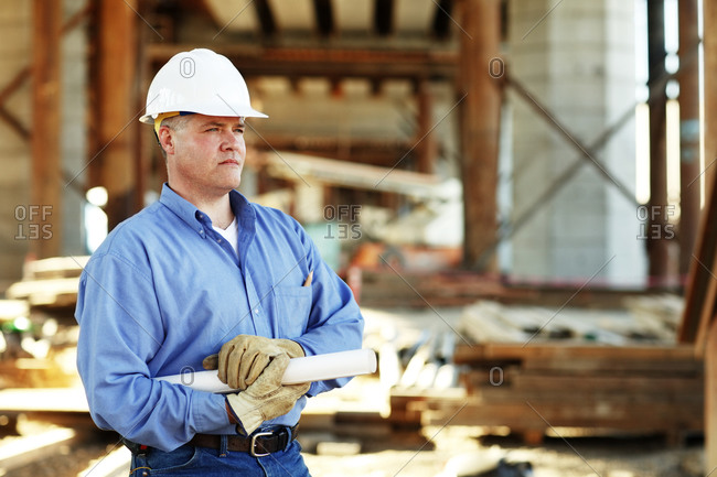 Male construction foreman holding plans looking off camera