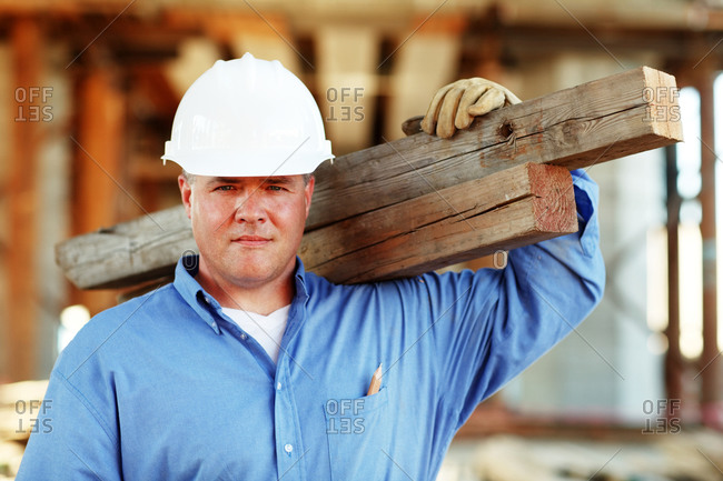 Male construction foreman holding lumber looking at camera