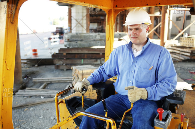 Male construction foreman sitting in a construction loader