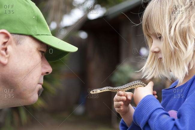 Father and daughter holding a gopher snake in the garden