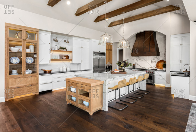 Kitchen in luxury home with large island and hardwood floors