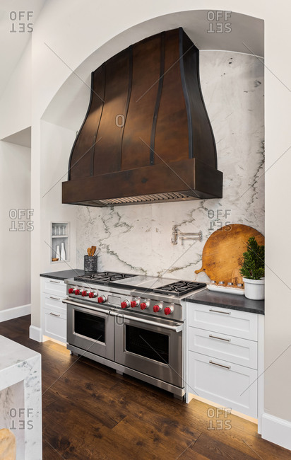 Beautiful stainless steel oven and large range hood in new luxury home