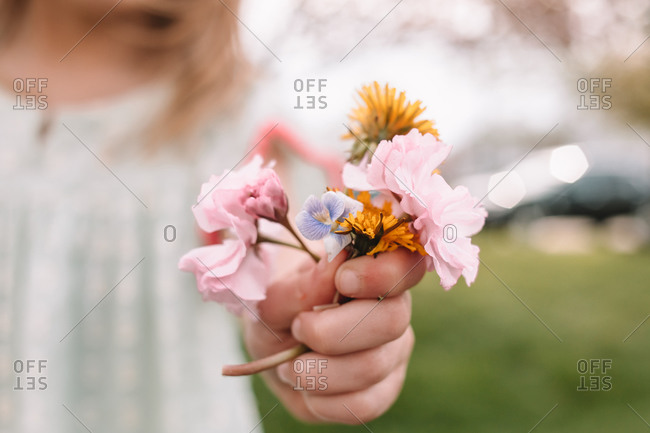 Toddler girl holding a small bouquet of wildflowers and weeds