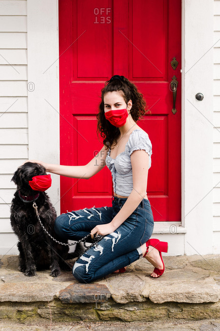 Young stylish woman and dog wearing mask during COVID19 pandemic