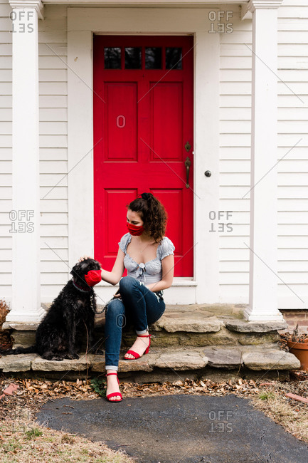 Young woman and dog wearing red mask during COVID-19 pandemic