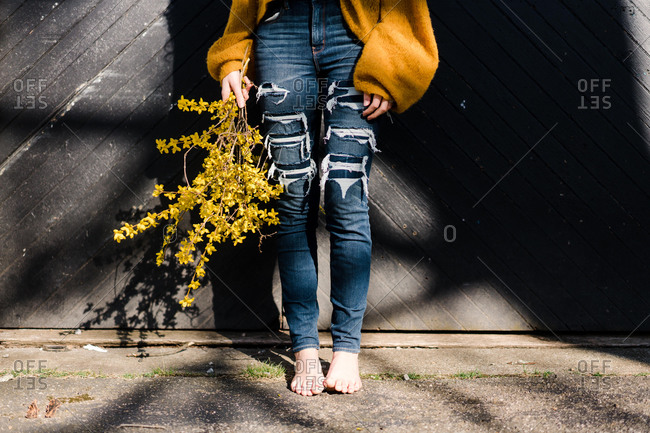 Young woman holding forsythia in pretty sunlight