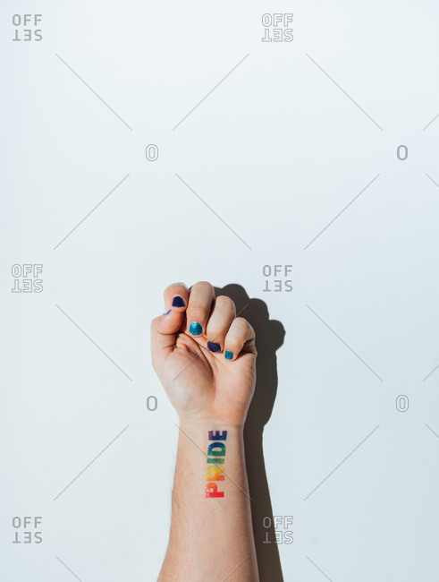 Gay guy's hand with a tattoo that says pride and nail polish.