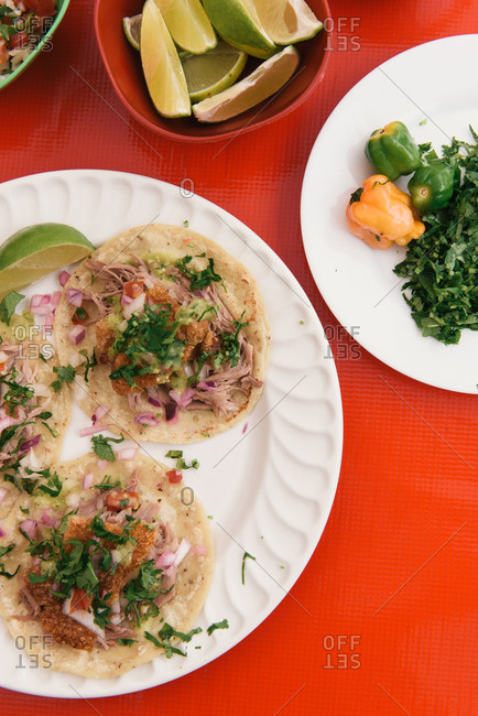 Overhead of a plate of tacos and ingredients at road side in Tulum