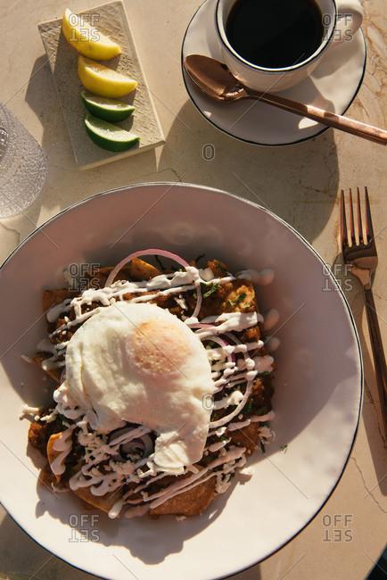 Overhead of Chilaquiles and coffee breakfast on outdoor veranda