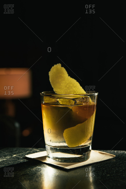 Old fashioned cocktail with citrus in sun beam at bar top