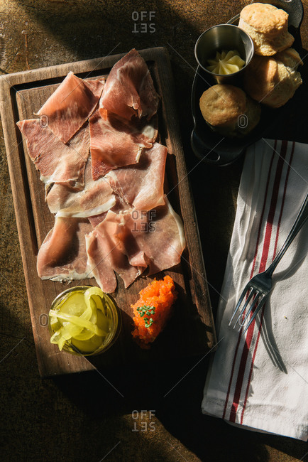 Slices of prosciutto and baskets of biscuits with pickled vegetables
