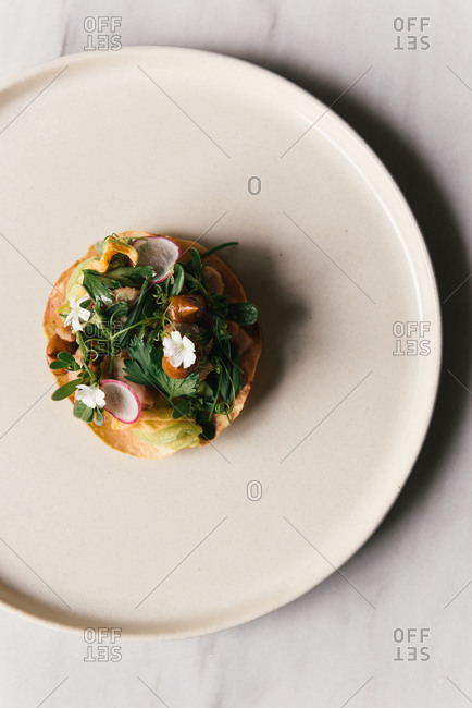 Artful tostada of sweet breads and greens at fancy Mexican restaurant