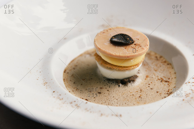 Side view of gourmet foie gras and truffle dish with eggs