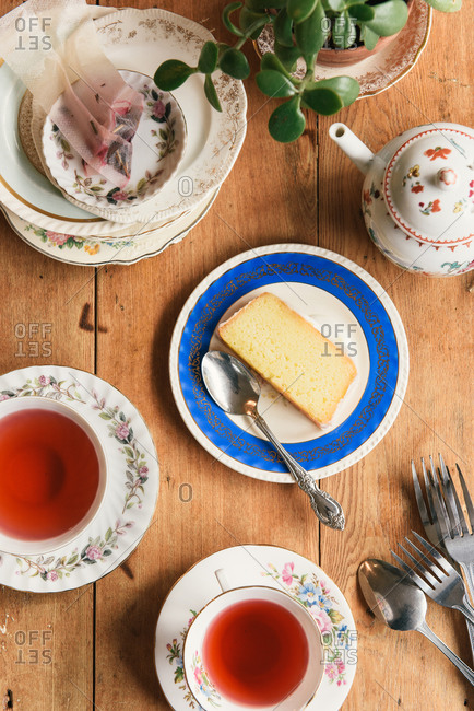 Overhead of tea time at a cafe with cake and teapots