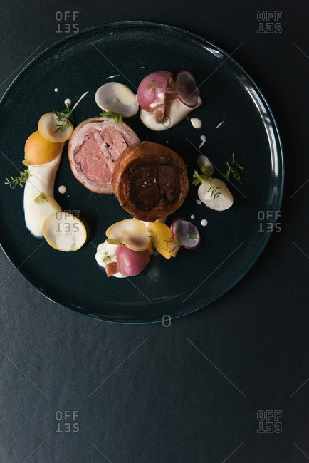 Cured ham slices with sauces and vegetables at fine dining restaurant