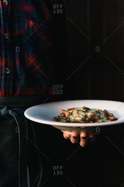Waiter holding a plate of handmade pasta at Italian restaurant