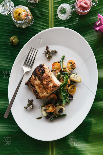 White fish and fresh garden vegetables on Caribbean tropical palm leaf