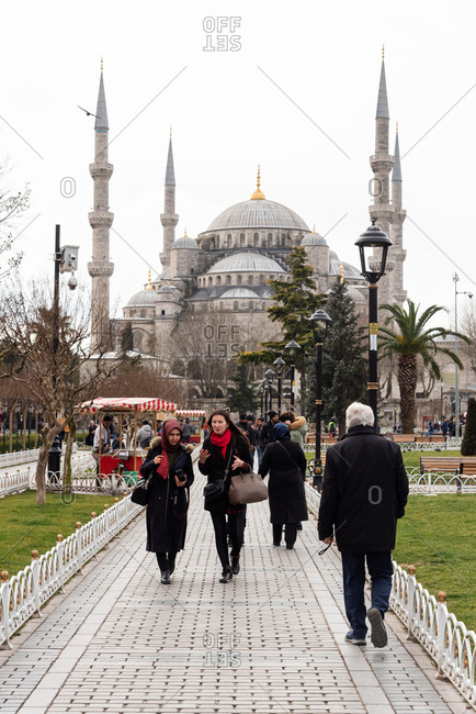 February 19, 2018: People walking across the square in front of the Sultan Ahmed Mosque. Istanbul, Turkey