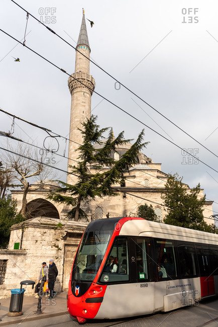February 21, 2018: Tram passing near a mosque in Sultanhamet district. Istanbul, Turkey