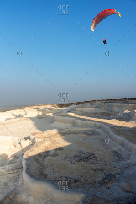 Men go paragliding over natural pools in limestone in Pamukkale, Turkey