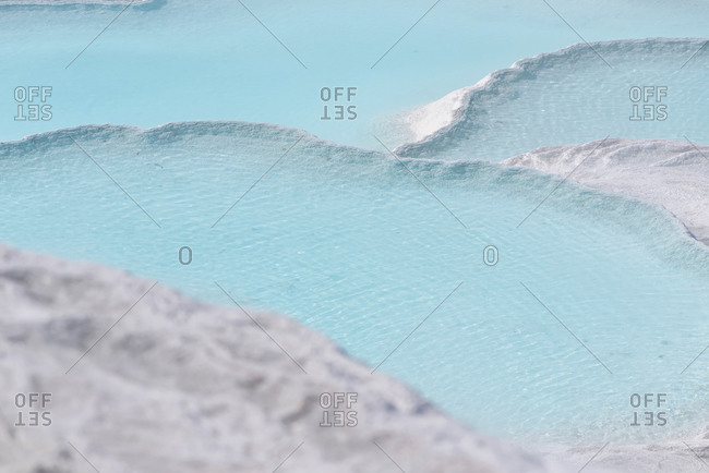 Blue steamy water of the spring in limestone pools in Pamukkale, Turkey