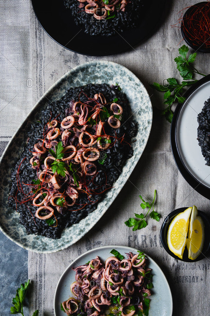 Overhead view of black risotto with cuttlefish ink and squid salad