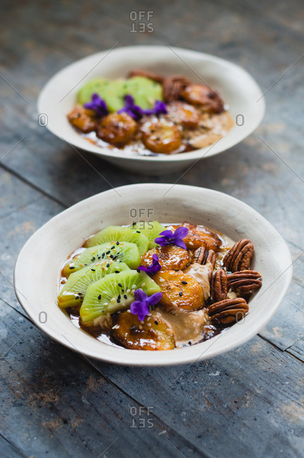 Warm oatmeal porridge with caramelized bananas, pecan nuts, tahini and kiwi on rustic wood surface