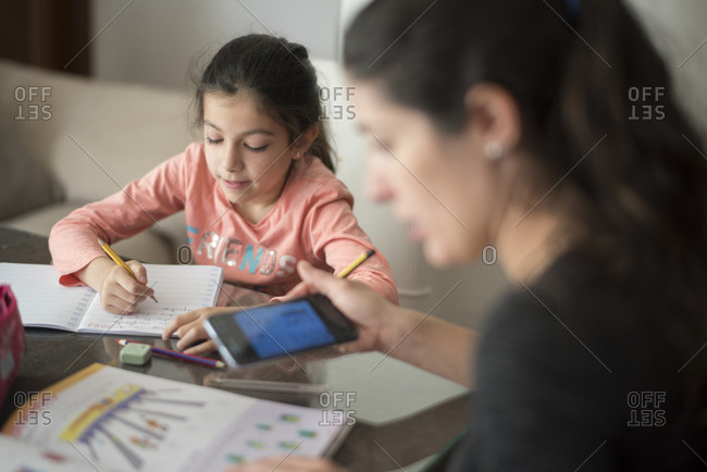 Mother using cell phone white helping little daughter do homework at home