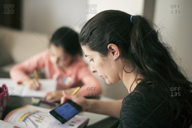 Mother using a smartphone white helping little daughter do homework at home