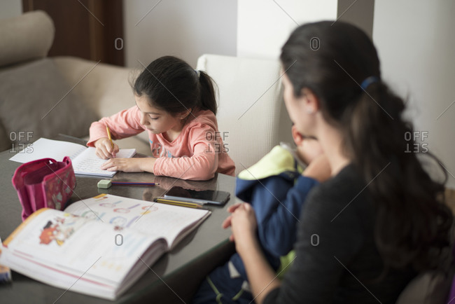 Mother holding toddler while helping her daughter doing homework