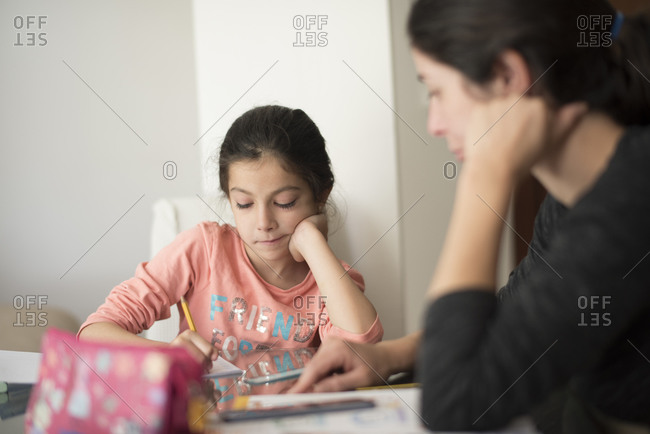 Mother helping her young daughter do homework at home