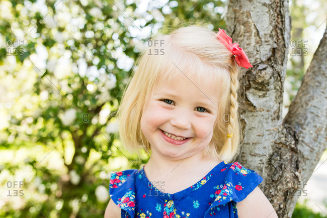 Portrait of an adorable little blonde girl standing by tree