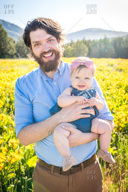 Father holding baby girl in front of a field filled with yellow flowers