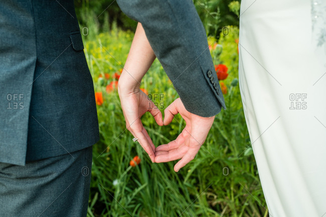 Couple making heart with their hands on wedding day