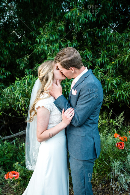 Bride and groom kissing in front of greenery and poppies
