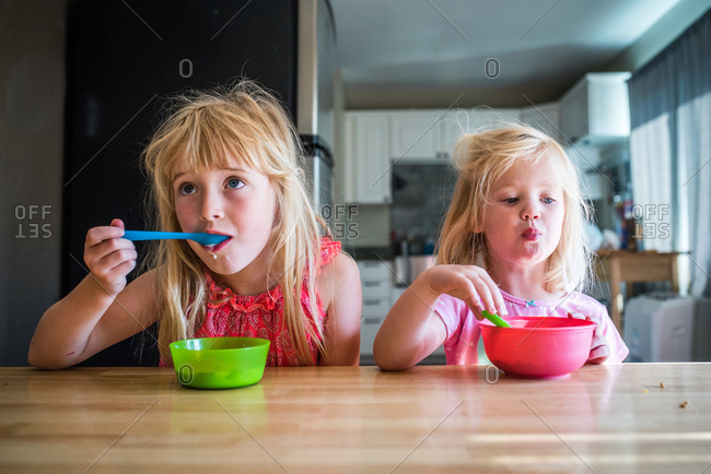 Two little girls eating cereal in the morning