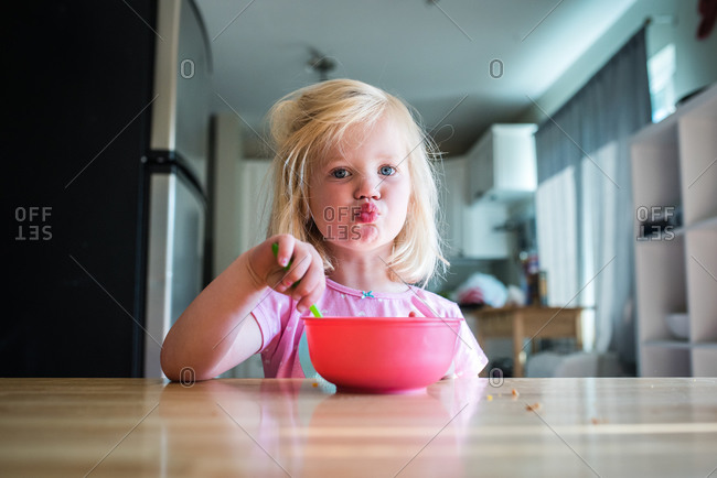 Little girl pursing lips while eating cereal