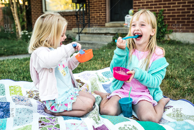 Two girls eating ice cream on a blanket outdoors