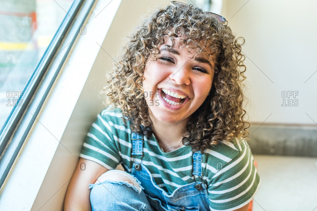 Happy young woman with curly brown hair smiling